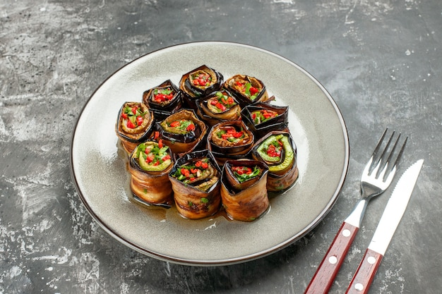 Rolos de berinjela recheada de vista inferior em prato oval branco garfo e faca em fundo cinza