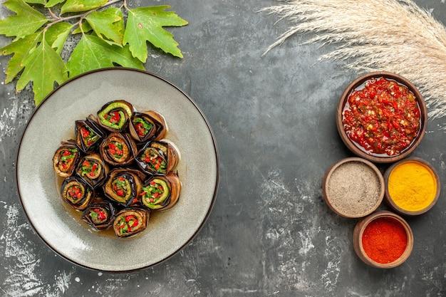 Rolos de berinjela recheada em prato branco, temperos diferentes em tigelas adjika em fundo cinza espaço livre