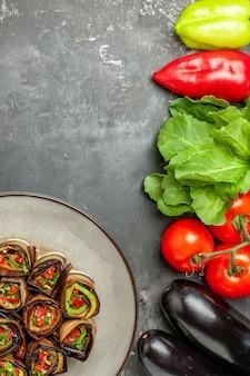 Rolos de berinjela recheada em prato branco tomates pimentas berinjelas verdes na superfície cinza