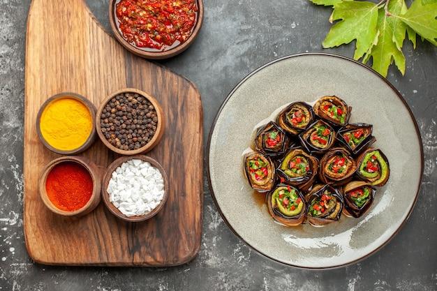 Rolos de berinjela recheada em prato oval branco com diferentes especiarias em tigelas em uma tábua de servir de madeira com alça adjika em fundo cinza