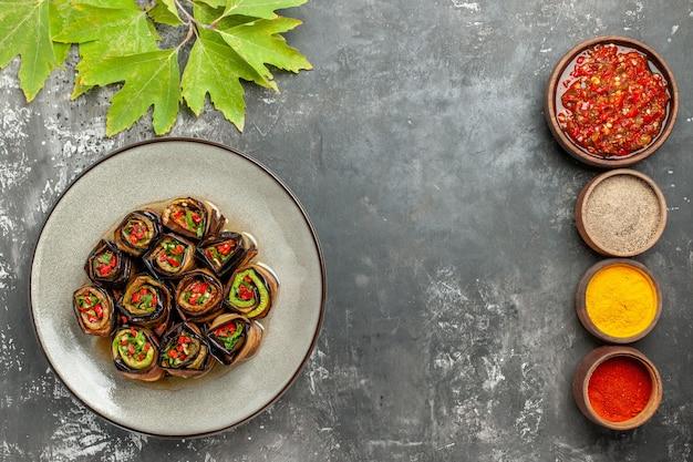 Rolos de berinjela recheada em um prato branco com diferentes especiarias adjika em pequenas tigelas em fundo cinza lugar livre vista de cima