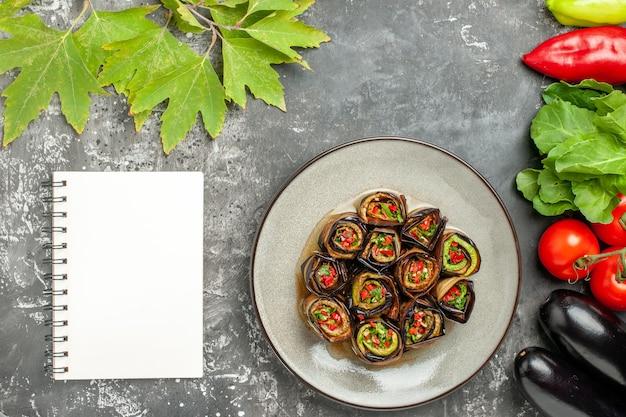 Rolos de berinjela recheada em um prato branco tomate pimentas berinjelas um caderno em fundo cinza foto de prato