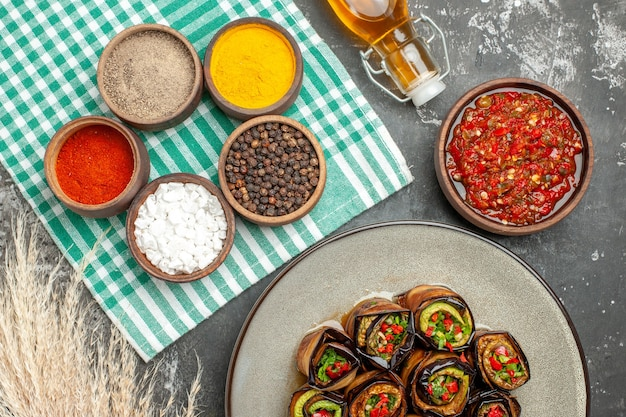 Rolos de berinjela recheada em um prato oval branco adjika em uma tigela pequena toalha de mesa branco turquesa com óleo de especiarias diferentes em fundo cinza.