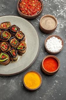 Rolos de berinjela recheada em um prato oval branco com especiarias em pequenas tigelas sal pimenta pimenta vermelha cúrcuma adjika na superfície cinza