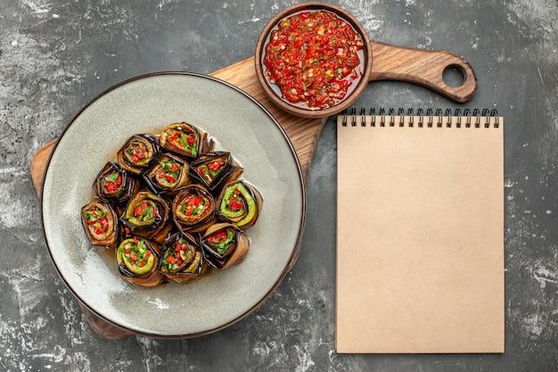 Rolos de berinjela recheada em um prato oval branco com pimenta preta em uma tigela em uma tábua de servir de madeira com alça adjika um caderno em fundo cinza