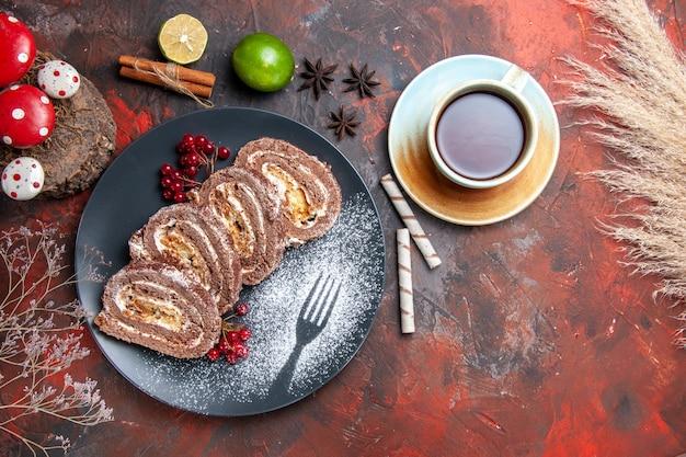 Rolos de biscoito gostoso com chá em fundo escuro, vista de cima