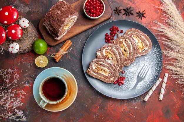 Rolos de biscoito gostoso com uma xícara de chá em fundo escuro, vista de cima