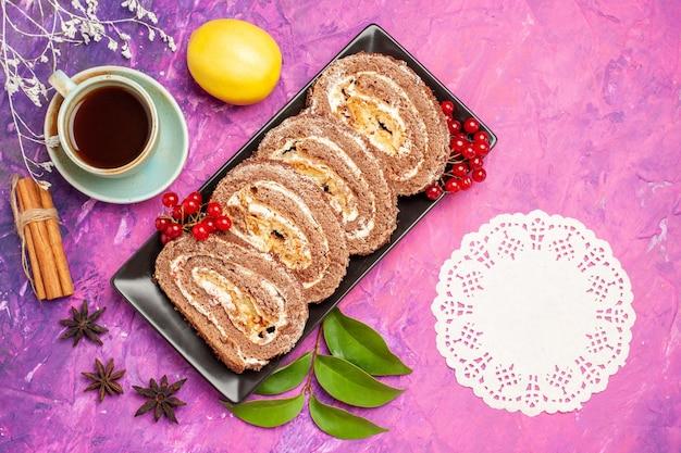Rolos de biscoito gostoso com uma xícara de chá no fundo rosa