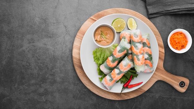 Rolos de camarão com molho no prato com espaço de cópia