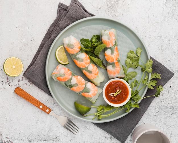 Rolos de camarão fresco no prato com molho