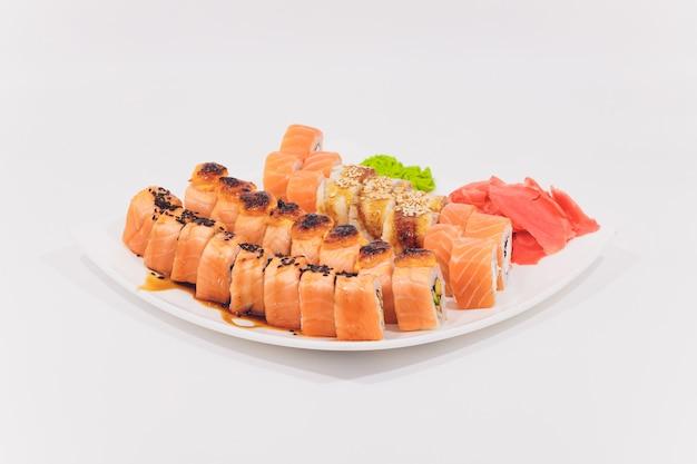 Rolos de caranguejo, salmão, queijo creme e pepino, isolados no fundo branco.