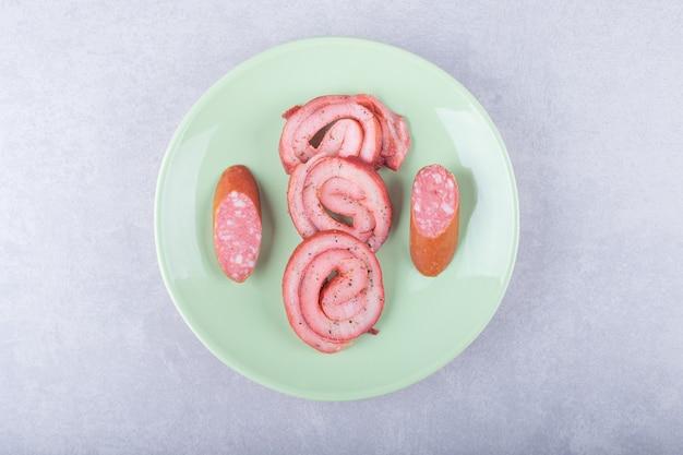 Rolos de carne defumada e salsichas na placa verde.