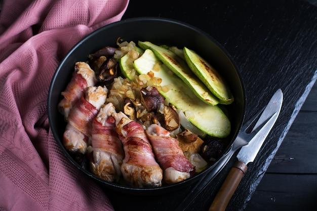 Rolos de carne grelhada envolvidos em tiras de bacon e fatias de medula