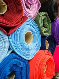 Rolos de close-up de tecido multicolorido brilhante. muitos tecidos diferentes estão enrolados e espalhados nas prateleiras.