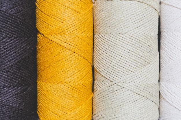 Rolos de cordas de crochê nas cores preto, amarelo e menta