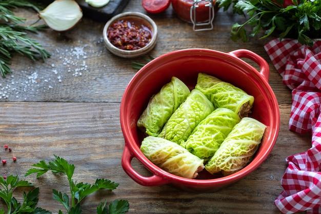 Rolos de couve lombarda recheados com carne, arroz e legumes em uma mesa rústica