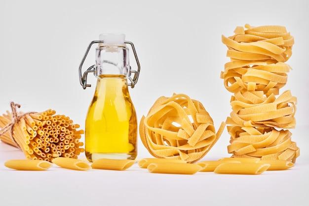 Rolos de espaguete com uma garrafa de óleo.