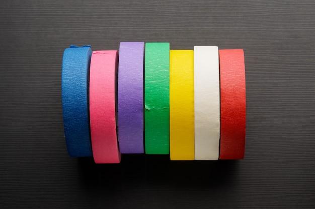 Rolos de fita adesiva colorida sobre fundo escuro de madeira. vista do topo.