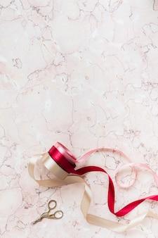 Rolos de fita em um fundo de mármore rosa