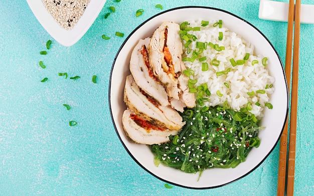 Rolos de frango, arroz, chuka e cebola verde em uma tigela branca com pauzinhos