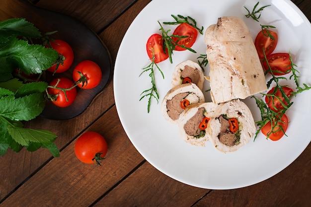 Rolos de frango assado dieta fígado recheado, pimentão e ervas com uma salada de tomate e rúcula. menu dietético. nutrição apropriada. vista do topo