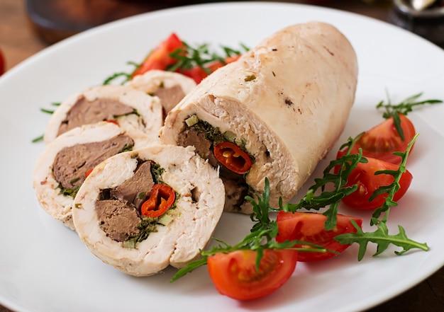 Rolos de frango assado dieta fígado recheado, pimentão e ervas com uma salada de tomate e rúcula. menu dietético. nutrição apropriada.