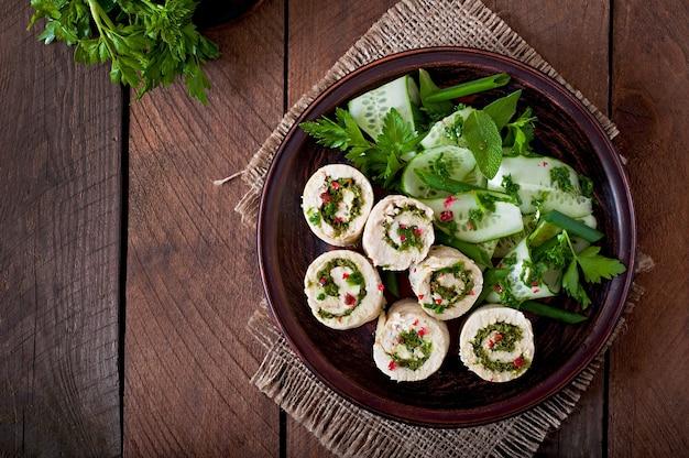 Rolos de frango cozido no vapor com verduras e salada de legumes fresca em um prato marrom