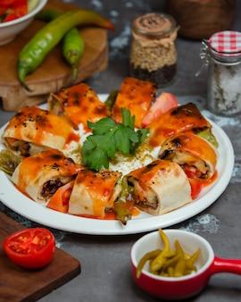 Rolos de kebab beyti servidos em pão sírio com legumes assados e molho de tomate