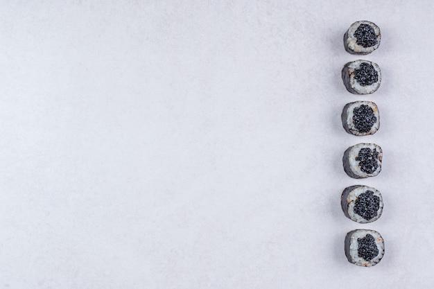 Rolos de maki decorados com caviar preto sobre fundo branco.