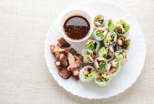 Rolos de mola asiáticos assorted frescos com carne de porco grelhada, legume fresco. prato saudável e delicioso