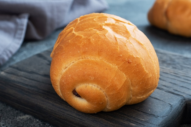 Rolos de pão de trigo fresco. rolos para cachorro-quente ou hambúrguer. espaço de cópia de fundo escuro.
