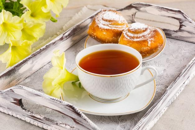 Rolos de pão doce de canela e chá na bandeja de servir vintage