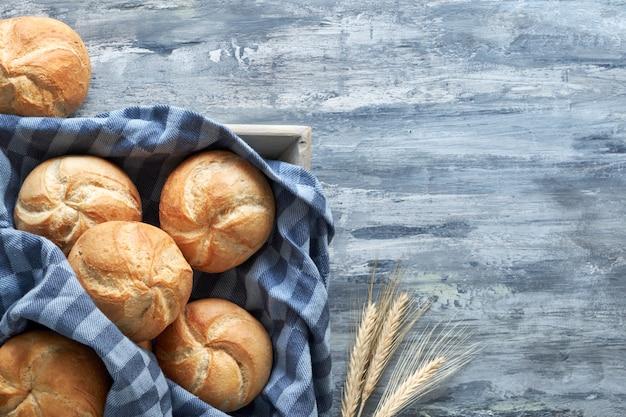 Rolos de pão redondo duro, conhecidos como rolos kaiser ou viena na toalha de linho