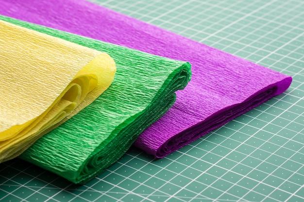 Rolos de papéis ondulados diferentes na esteira de corte antes da modelagem
