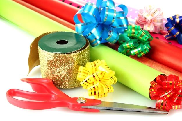 Rolos de papel de embrulho de natal com fitas, laços isolados no branco