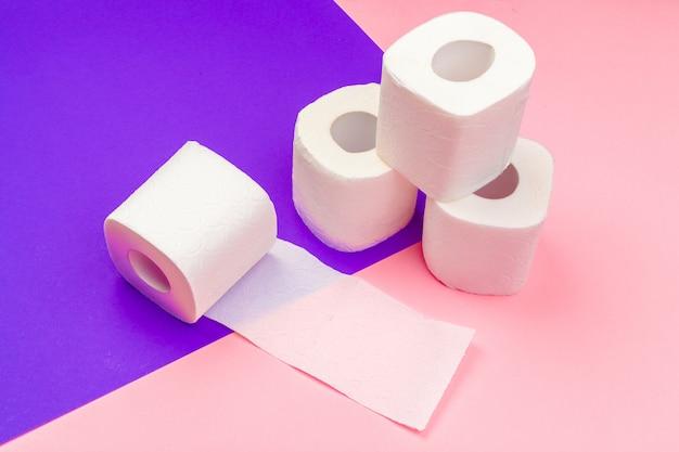 Rolos de papel higiênico branco sobre fundo de bloco de cor brilhante