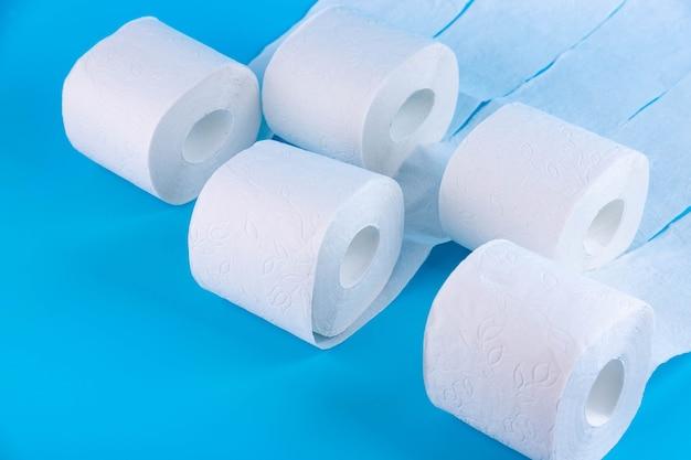 Rolos de papel higiênico branco sobre um fundo azul com lugar para texto, publicidade.