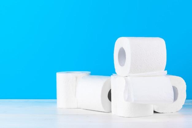 Rolos de papel higiênico empilhados contra azul