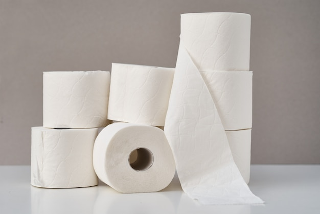 Rolos de papel higiênico empilhados em fundo cinza