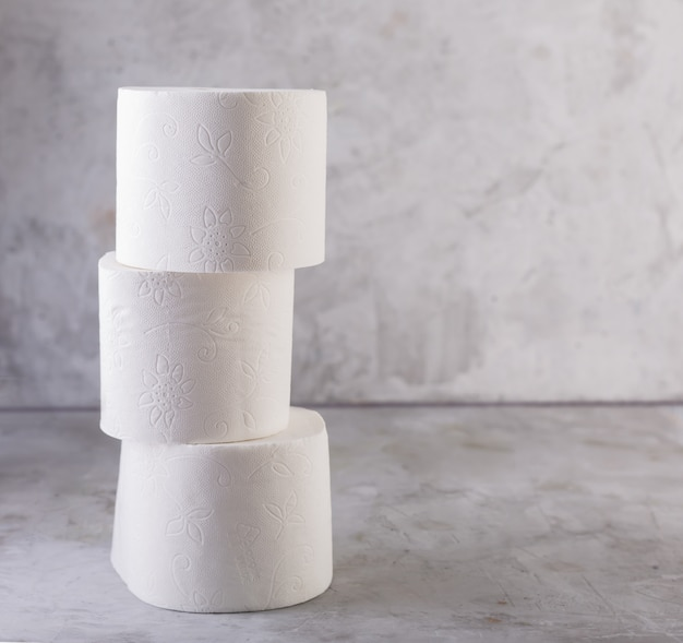 Rolos de papel higiênico empilhados sobre uma mesa de concreto cinza
