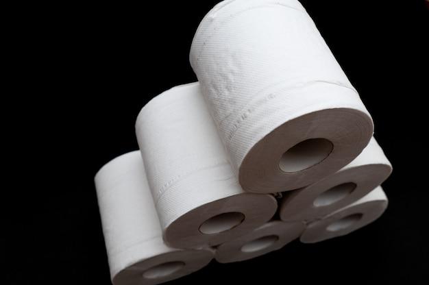 Rolos de papel higiênico isolados em um fundo preto em close