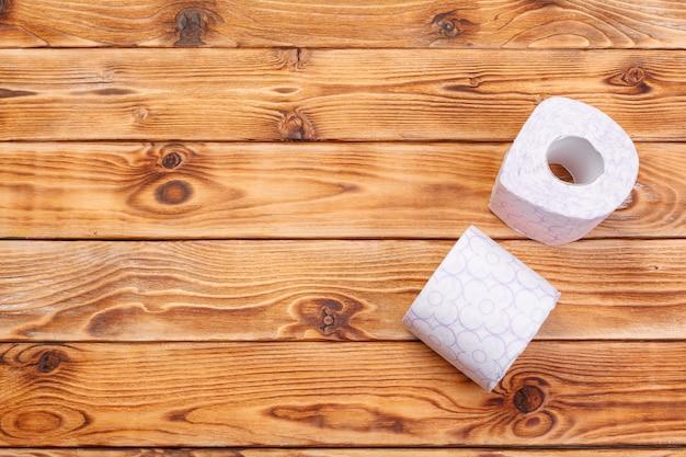 Rolos de papel higiênico na vista superior do plano de fundo de madeira