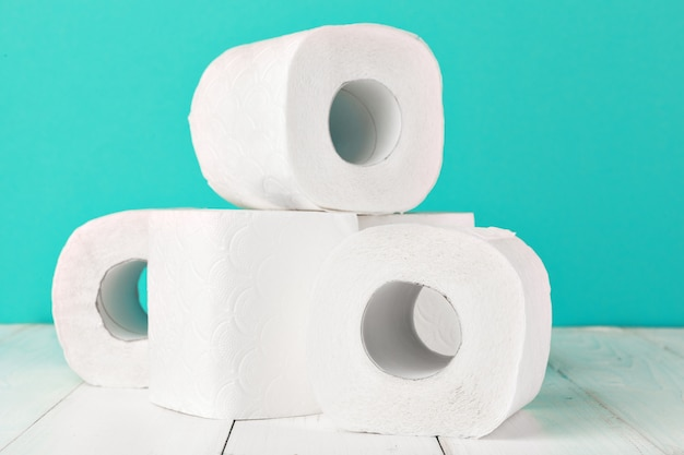 Rolos de papel higiênico no fundo brilhante turquesa