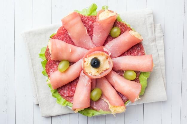 Rolos de presunto com queijo e salsicha em um prato