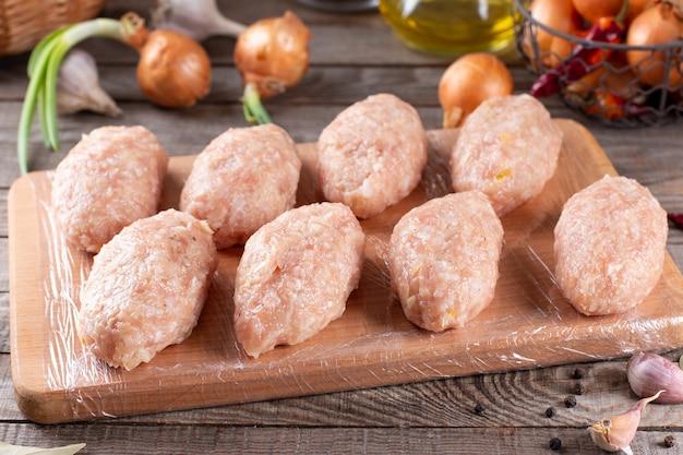 Rolos de repolho preguiçoso congelados crus repousam sobre uma placa de madeira na mesa da cozinha com verduras e legumes