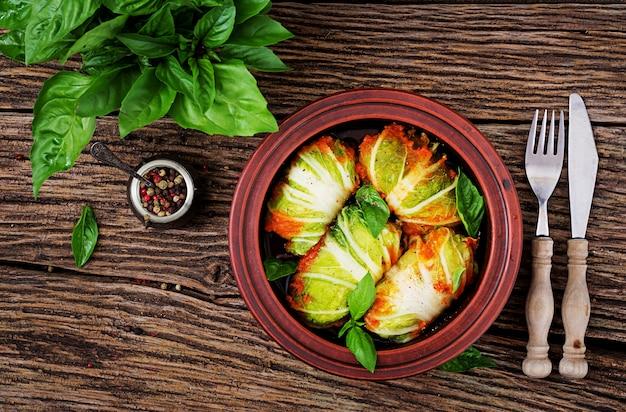 Rolos de repolho recheado com arroz com filé de frango em molho de tomate em uma mesa de madeira. comida saborosa. vista do topo. configuração plana