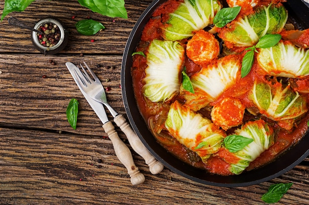 Rolos de repolho recheado com arroz com filé de frango em molho de tomate em uma mesa de madeira.