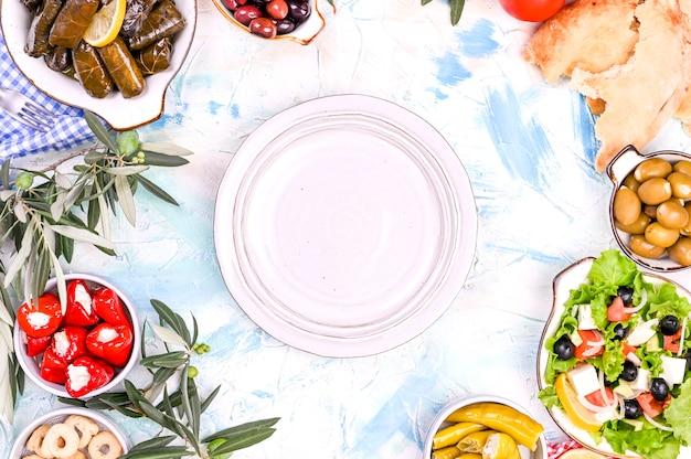 Rolos de repolho turco e vários petiscos da culinária nacional. arroz em folhas de uva e azeitonas. comida para um almoço oriental tradicional. espaço livre para texto, prato vazio