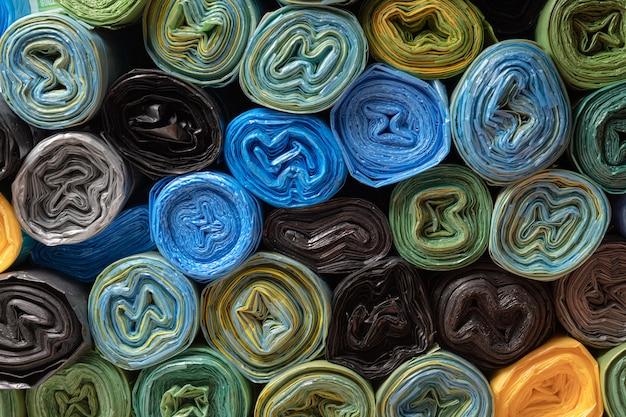 Rolos de sacolas plásticas. plano de fundo texturizado. muitos sacos enrolados multicoloridos para resíduos de construção.