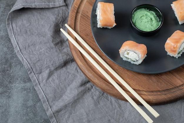 Rolos de salmão com cream cheese em uma placa preta com molho de wasabi.